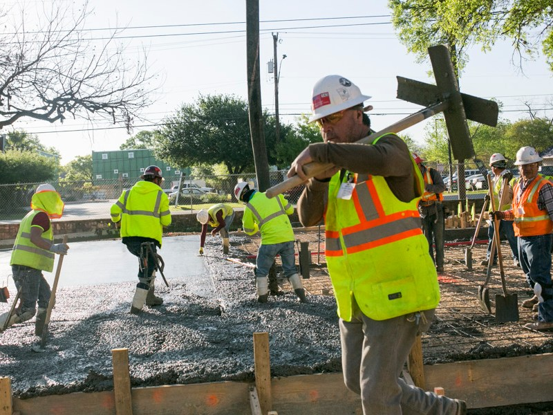 Construction workers pour concrete for the outside of the Mays Family Center. Photo by Kathryn Boyd-Batstone