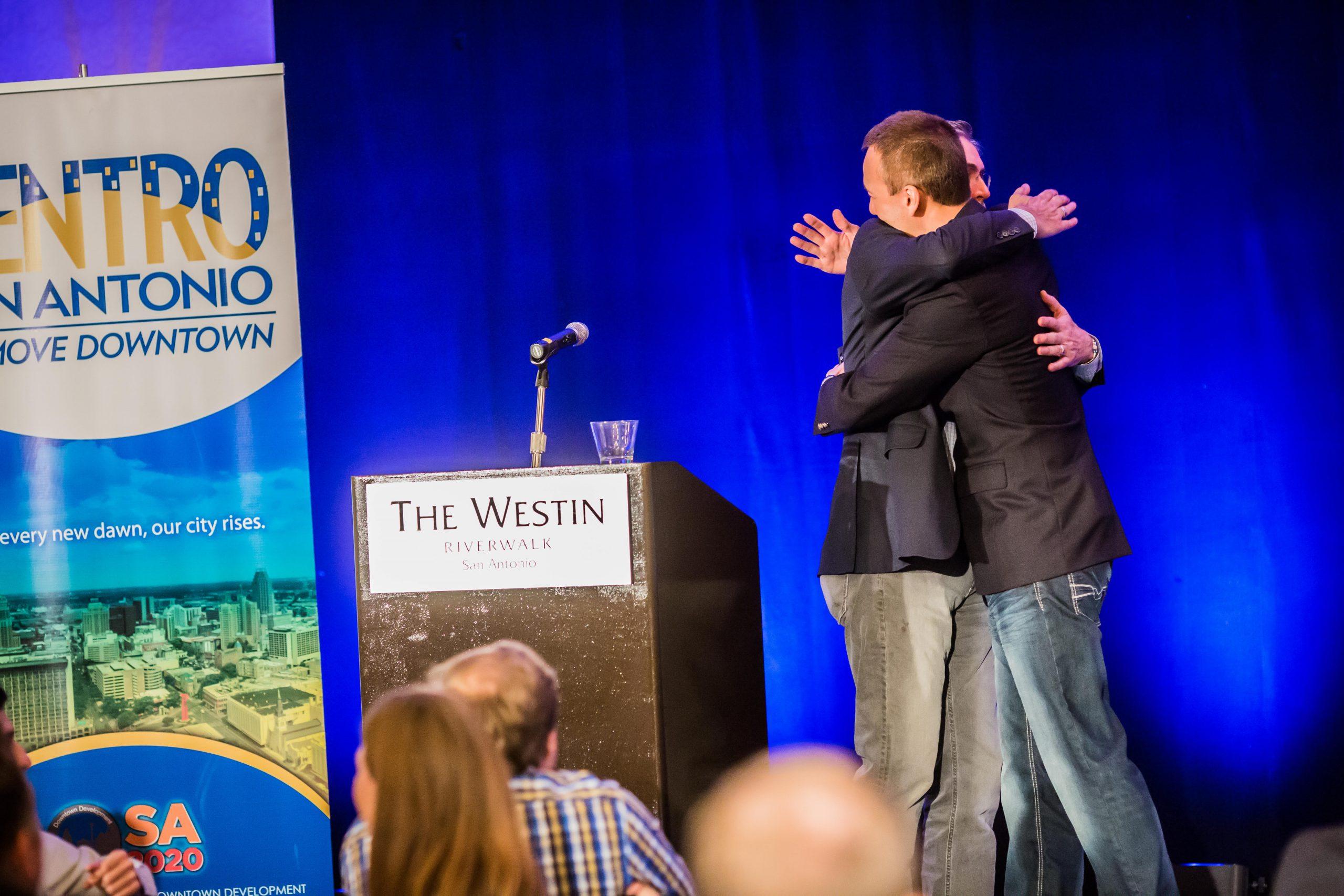 Centro San Antonio President and CEO Pat DiGiovanni (left) hugs author Peter Kageyama. Photo by Michael Cirlos for Centro San Antonio.