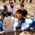 Ukaraine UIW student Rostyslav Fedyna (center) sings with Middle Eastern and African refugees. Photo by Sheena Maria Connell.