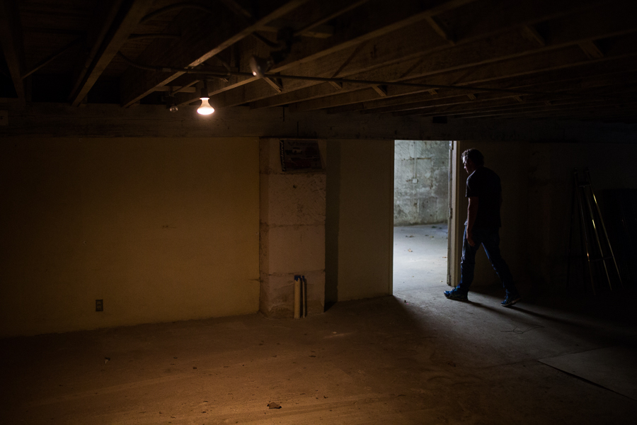 Lee Beekly walks through an empty basement that currently has no plans to accommodate guests due to a city ordinance requiring higher ceilings. Photo by Scott Ball.