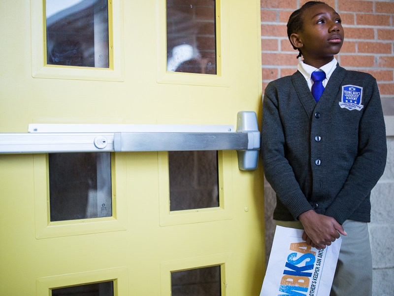 Cedric, a 6th grade student at YMLA waits by the door to greet guests. Photo by Scott Ball.