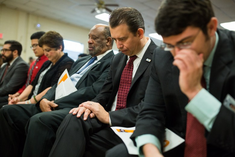 Pedro Martinez bows his head along with colleagues and SAISD board members. Photo by Scott Ball.