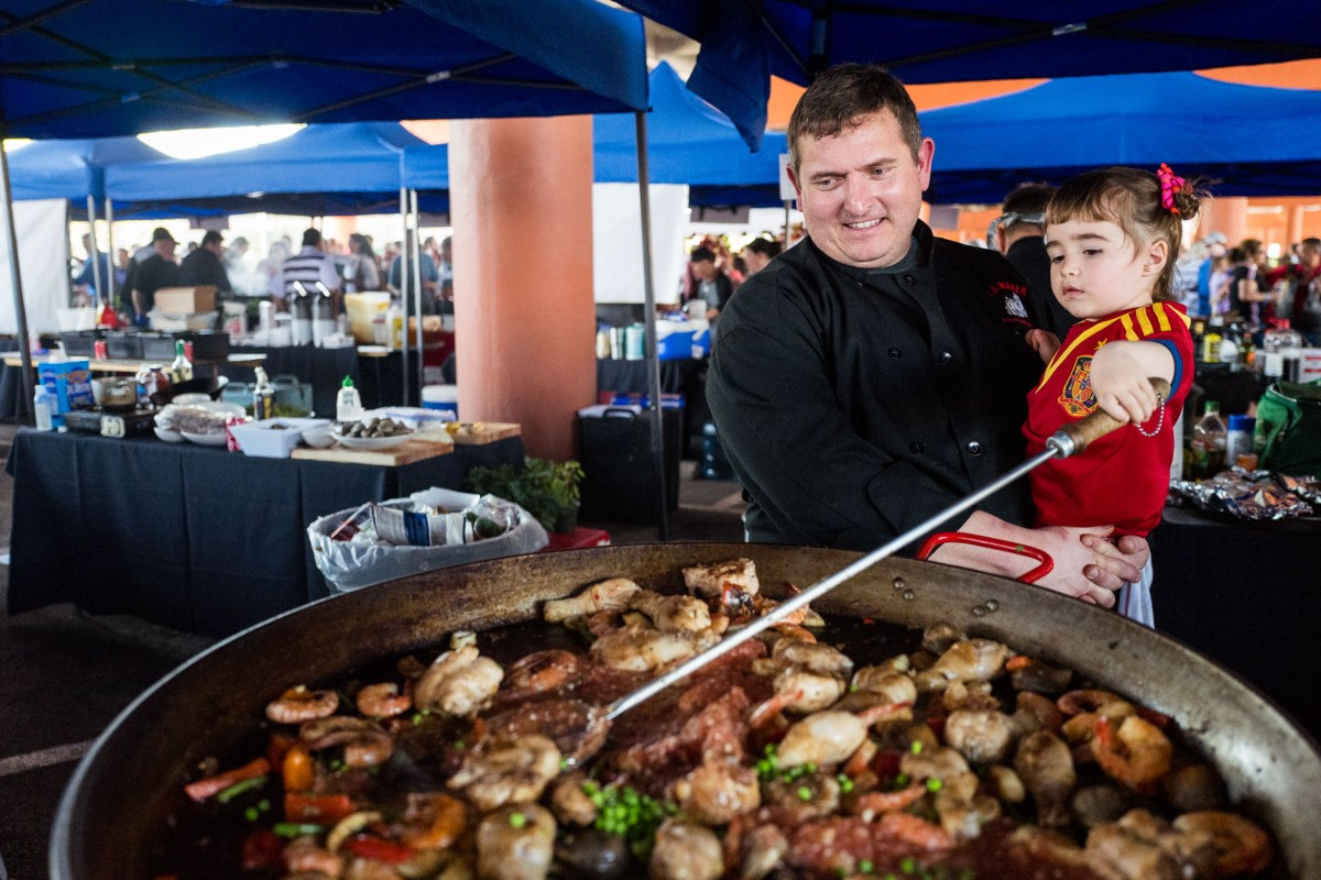 Las Masia Catalan Catering Chef Alejandro Rodriguez holds his daughter Sofia as she stirs the paella. Photo by Scott Ball.