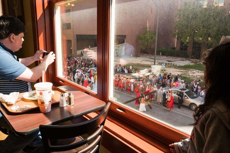 Diners at Bill Miller's Barbecue watch as the performance passes them on North Main Avenue. Photo by Scott Ball.