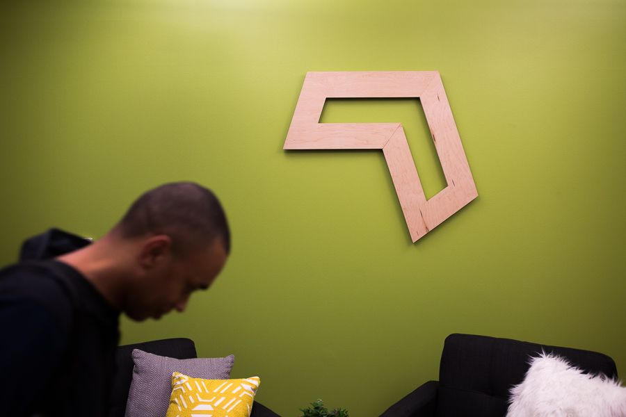 A Codeup student passes by the Codeup logo on the wall of their new facilities in the Vogue Building. Photo by Scott Ball.