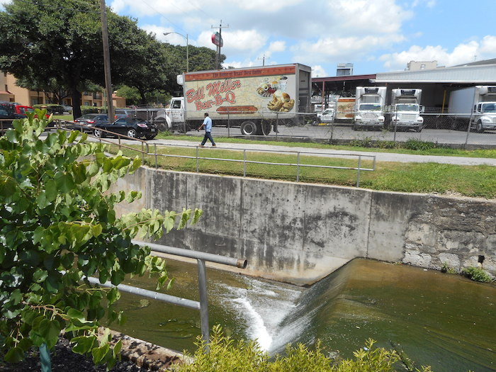 A worker walks by a waterfall just before the San Pedro Creek disappears under César E. Chávez Blvd. Writers and photographers are invited to explore the stream on April 9. Photo by Don Mathis.