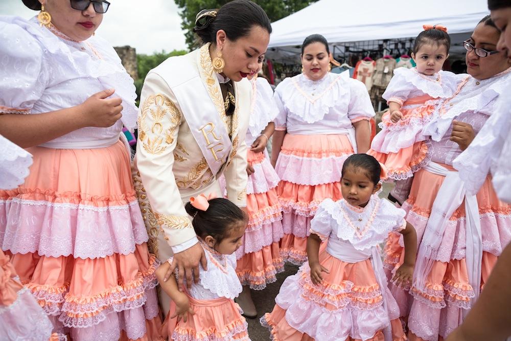 Queen Escaramuza Harley Jane De Luna gathers children for a group photo at the San Jose MissionFest. Photo by Michael Cirlos.