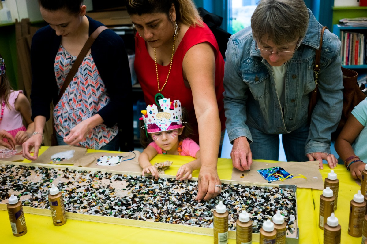 A family works on creating a glass mosaic at one of the craft stations. Photo by Kathryn Boyd-Batstone