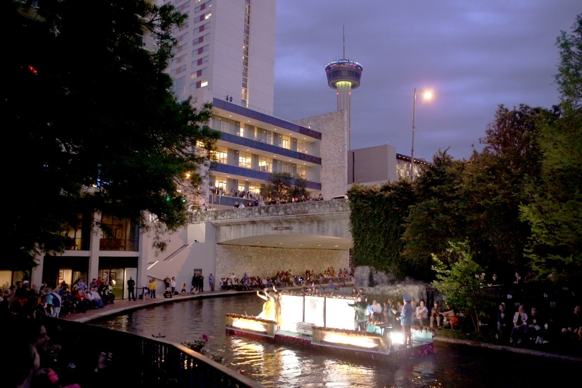 A boat goes down the Riverwalk as part of the Fiesta River Boat Parade. Photo by Kathryn Boyd-Batstone