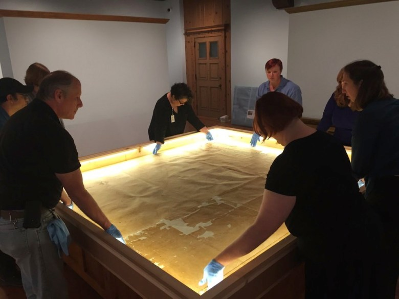 Witte Museum staff carefully installs the Stephen F. Austin's Connected Map of Austin's Colony, 1833-1837. Photo courtesy of the Witte.