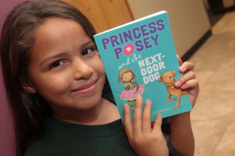 A young student in the Reading Buddies program poses with a book. Photo courtesy of San Antonio Youth Literacy.