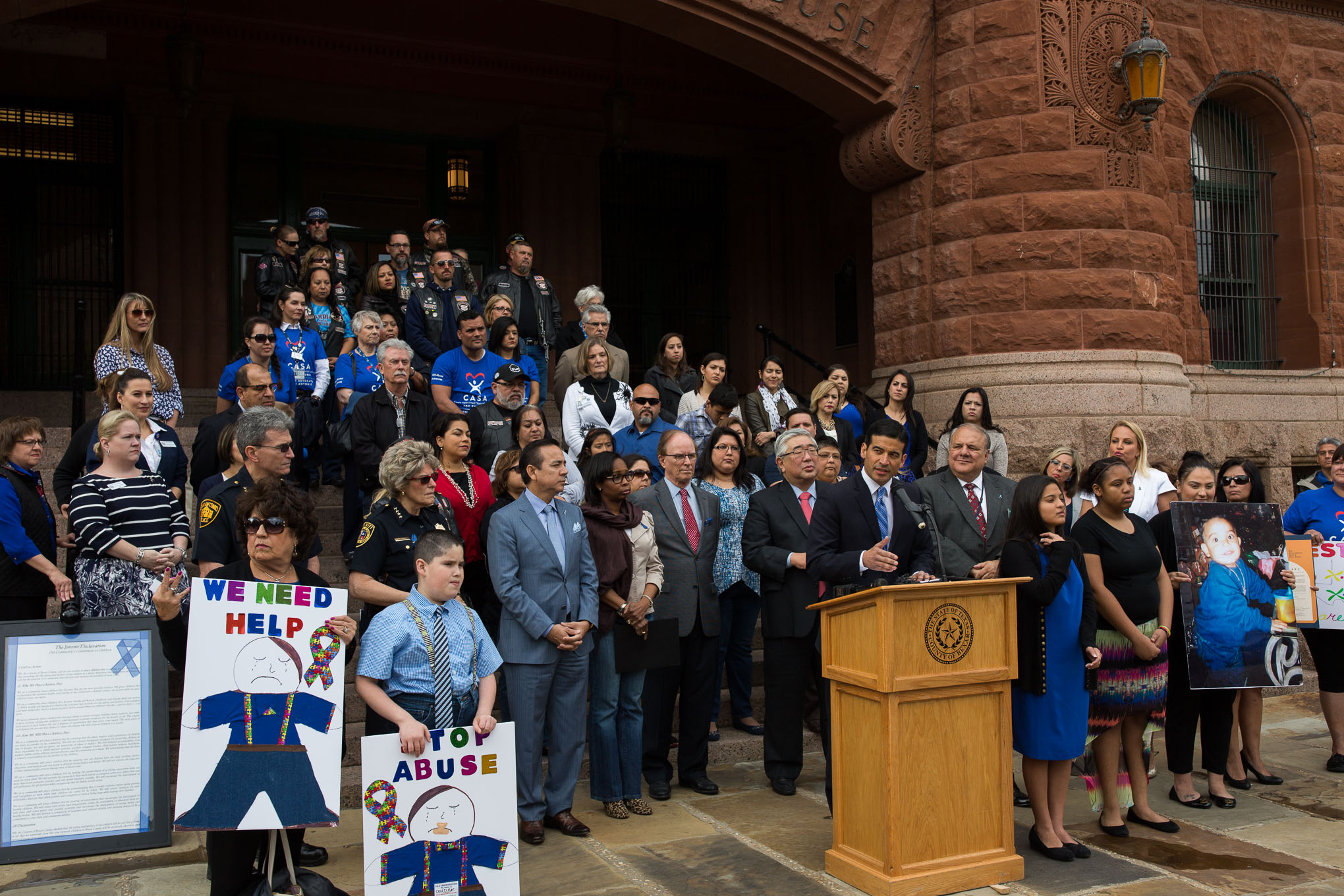 Bexar County District Attorney Nico LaHood speaks as child protection advocates stand behind him on the Bexar County Courthouse steps. Photo by Scott Ball.