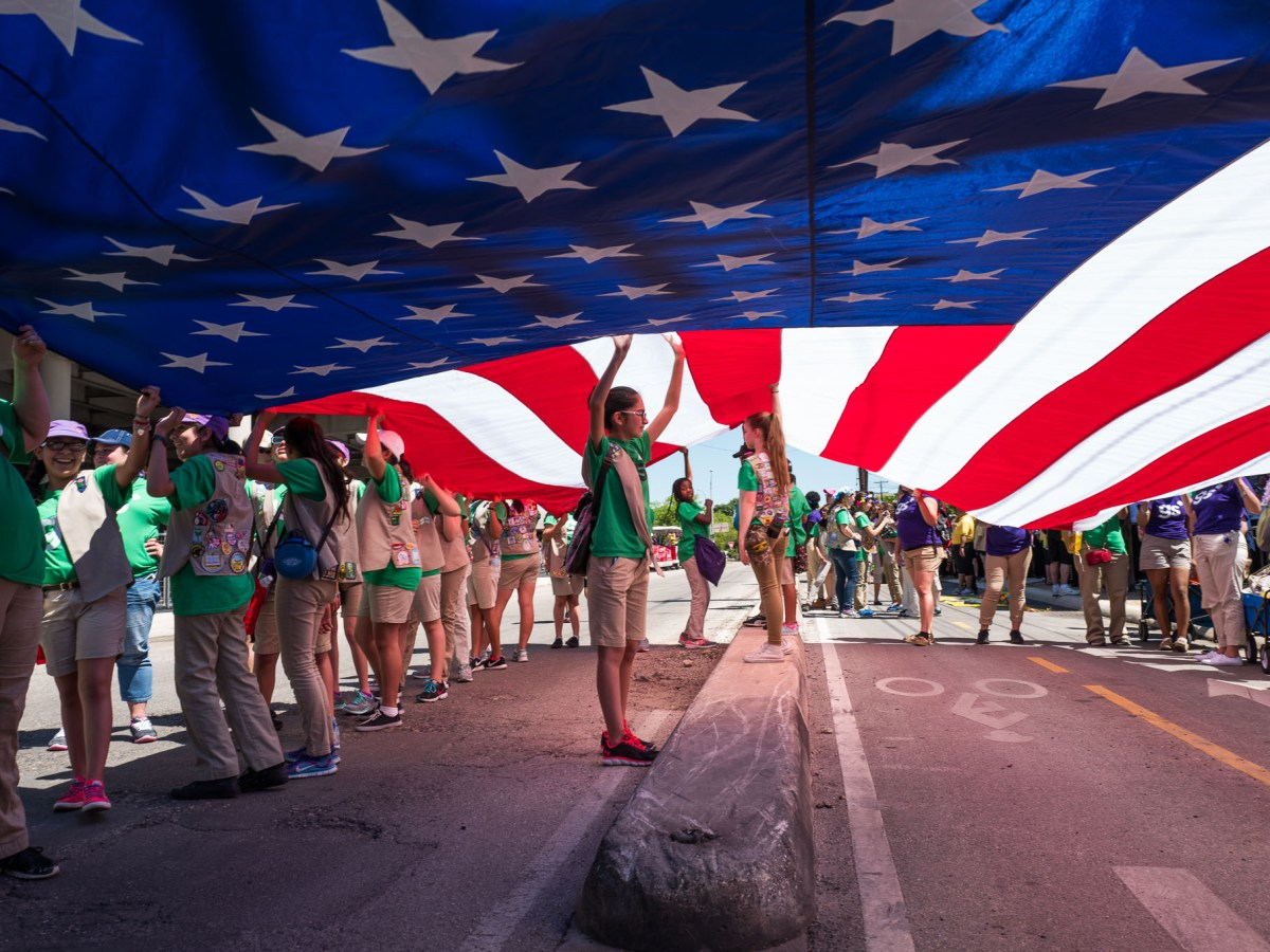 A local Girl Scout troop holds the American Flag while staging for the Battle of the Flowers Parade. Photo by Scott Ball.