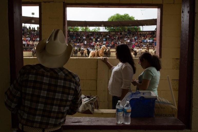 Spectators peer through a widow overlooking the charreada grounds. Photo by Scott Ball.