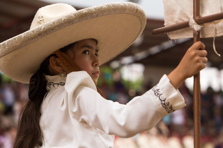 A young rider of the Escarmuzas Ogrullo Mexicano stands holding a flag during a ceremony preceding the event. Photo by Scott Ball.