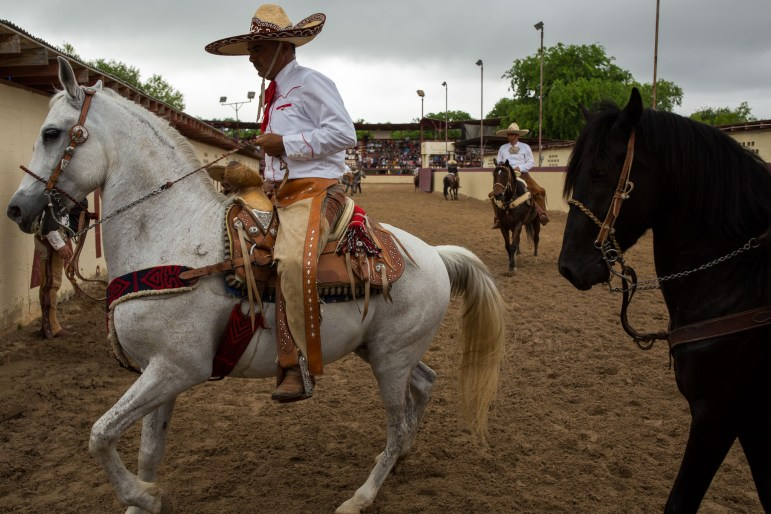 Charros and their horses gather at a gate exiting the grounds. Photo by Scott Ball.