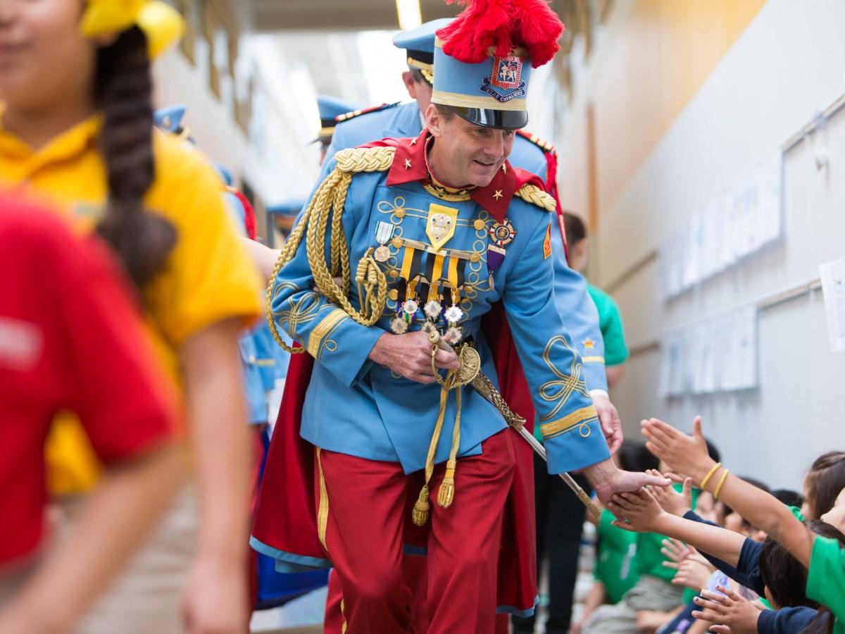 King Antonio R. Hunt Winton III high fives hallways lined with students at KIPP San Antonio on his way to the gymnasium. Photo by Scott Ball.