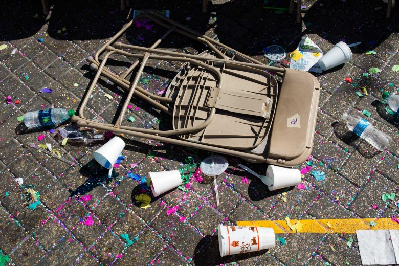 A chair lays on the street surrounded by cups and litter. Photo by Scott Ball.