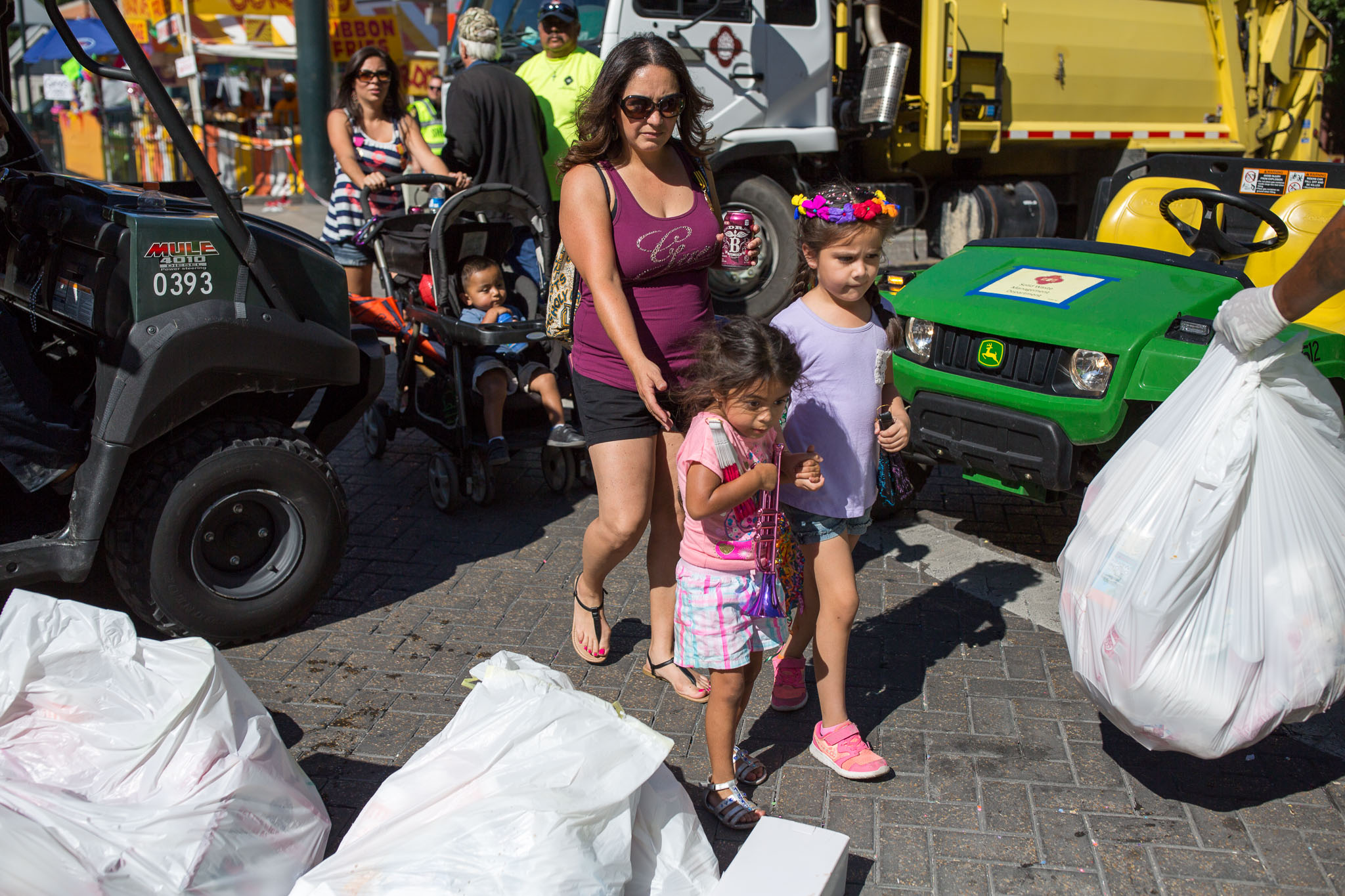 A family attempts to cross Commerce Street as bags of trash and work vehicles surround them. Photo by Scott Ball.