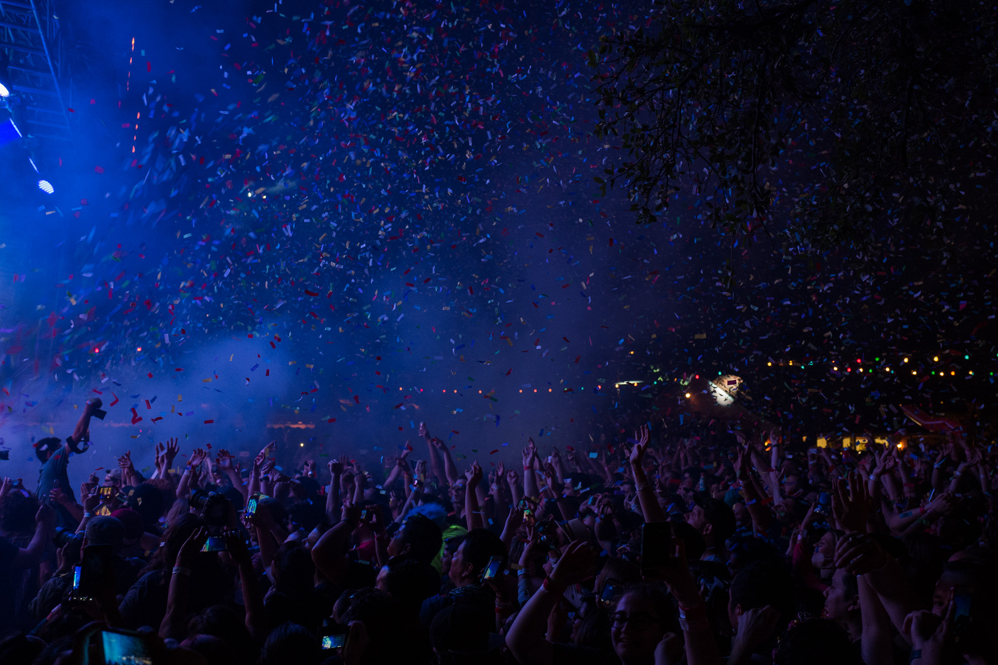 Masses of people lift their arms as confetti rains upon them. Photo by Scott Ball.