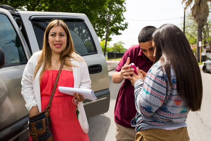 Christina Amador stands next to her vehicle after picking up her children from Rhodes Middle School Roy, 14 and Jacelle, 13. Photo by Scott Ball.