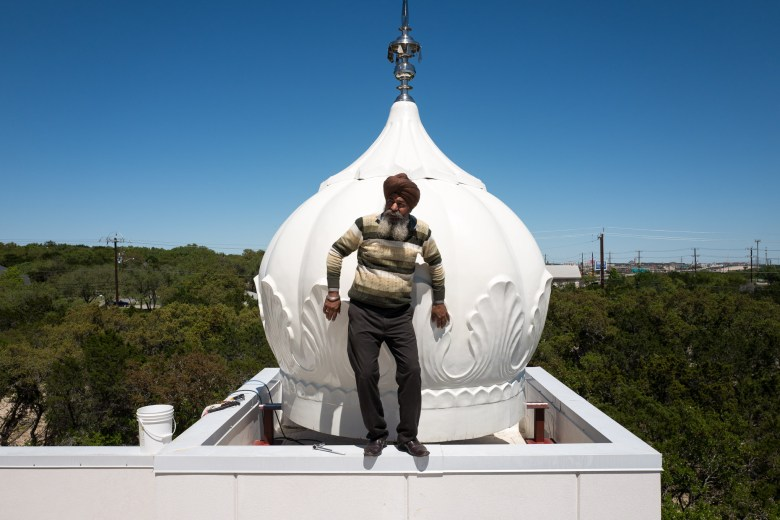 Artist Lahkvir Singh uses a recently installed gumbad to balance himself on the thin walls of the Gurdwara. Photo by Scott Ball.