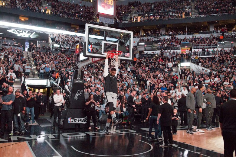 Tim Duncan hangs from the rim during the pre-game introductions. Photo by Scott Ball.