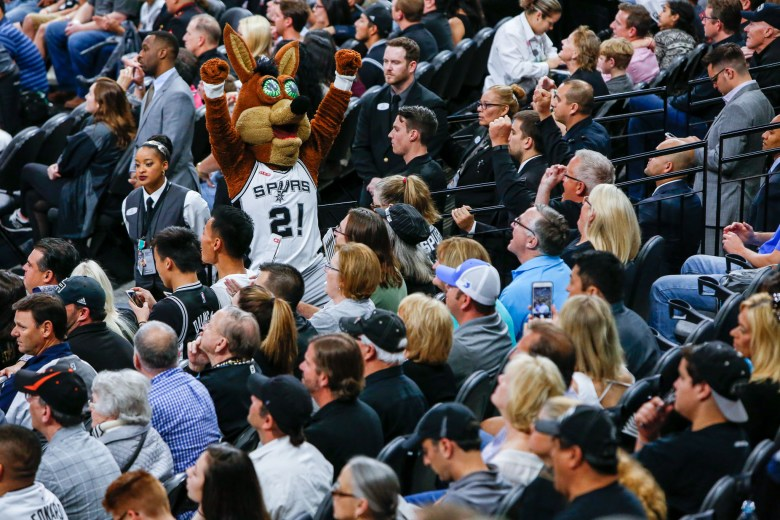 The Spurs Coyote raises his arms cheering a play. Photo by Scott Ball.