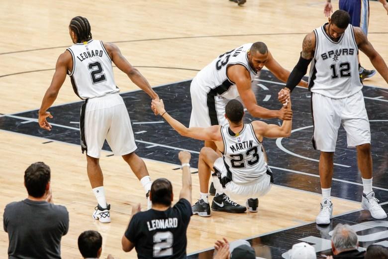 Spurs players Kawhi Leonard, Boris Diaw, and LaMarcus Aldridge help pick up Kevin Martin after a fall. Photo by Scott Ball.