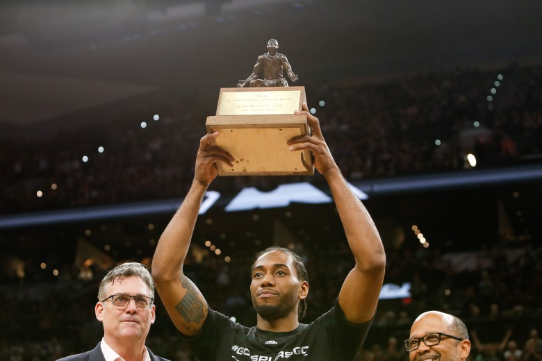 Spurs Forward and 2 time consecutive defensive player of the year Kawhi Leonard holds up his trophy he is presented. Photo by Scott Ball.