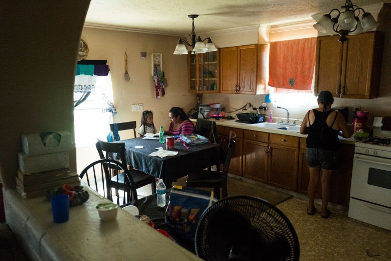 Romona spends with with Elizabeth while she is doing homework as her mother prepares food for the children. Photo by Scott Ball.