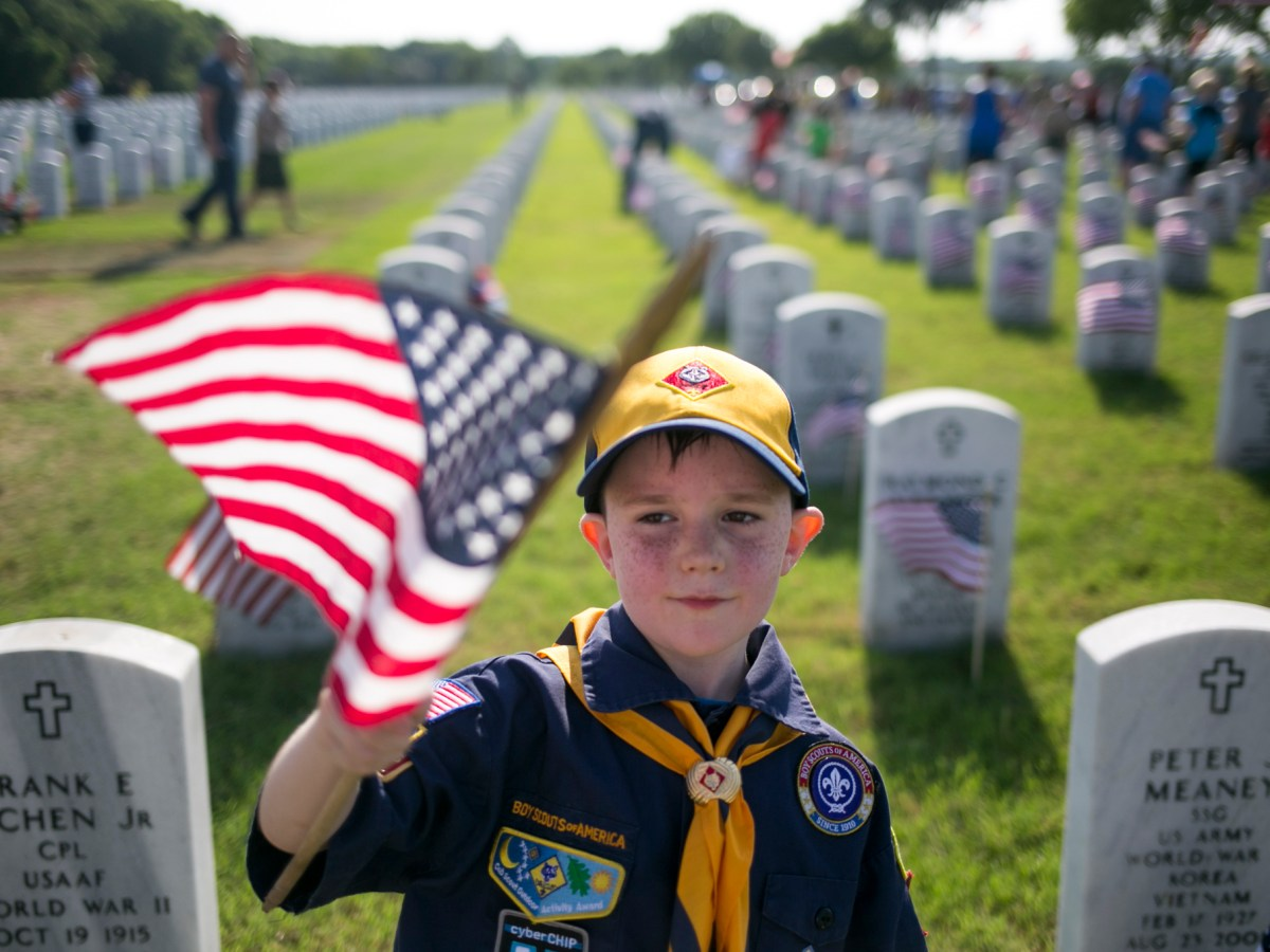 Gregory of Pack 285 leads his troop through the cemetery with a guiding flag. Photo by Kathryn Boyd-Batstone