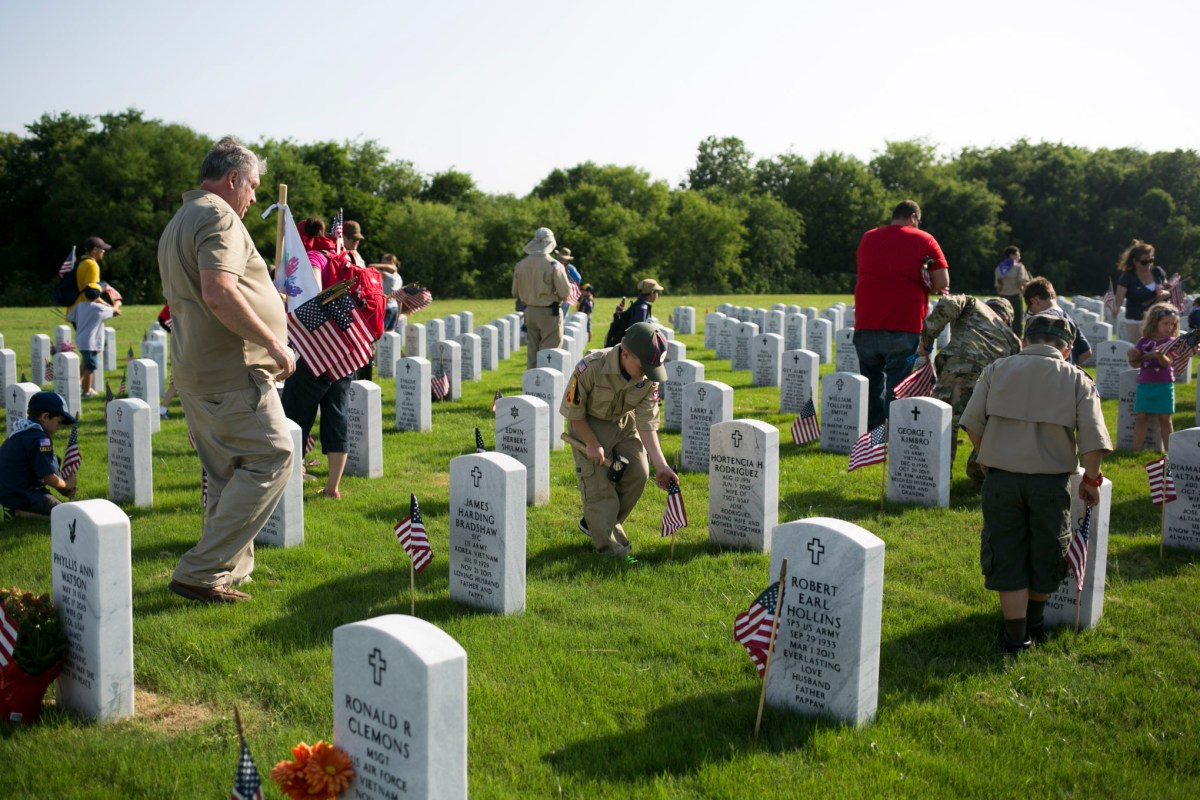 Hundreds of Boy and Girl Scouts place flags in one of headstones in honor of Memorial Day. Photo by Kathryn Boyd-Batstone