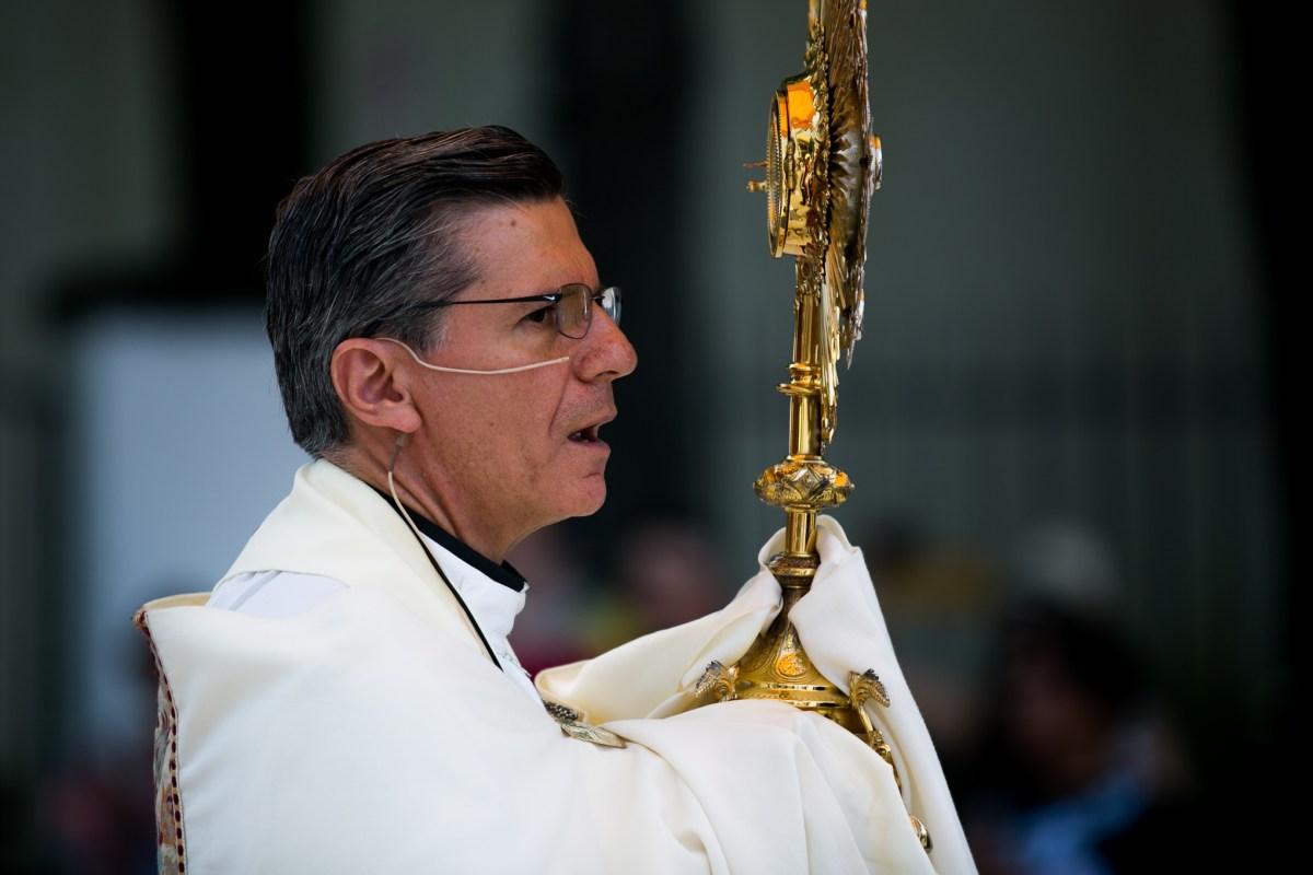Archbishop Gustavo García-Siller holds the Holy Eucharist. Photo by Kathryn Boyd-Batstone.