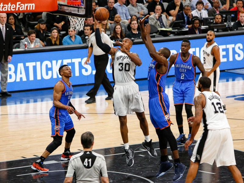 # 30 David West of the San Antonio Spurs goes for the lay-up through Oklahoma City defenders. Photo by Scott Ball.