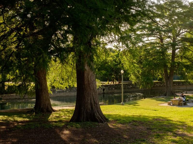 A family picnics along the San Antonio River in Brackenridge Park. Photo by Scott Ball.