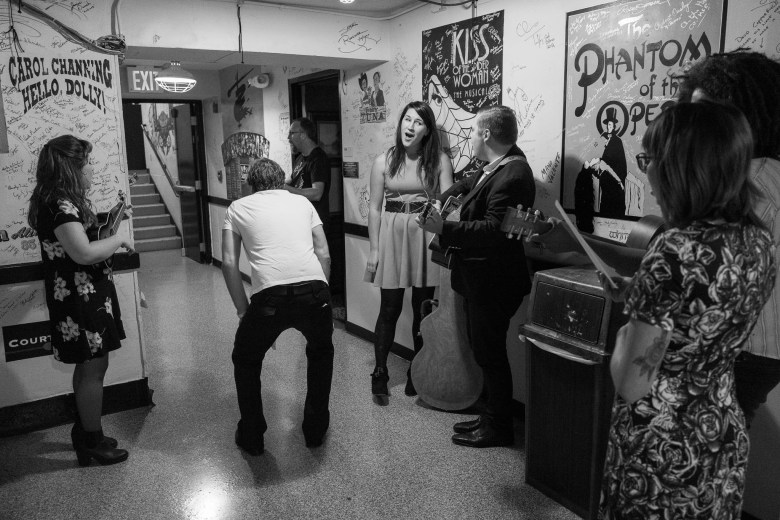 Erik Sanden (middle) bends over in excitement as local musicians recite famous songs by artists who had marked their signatures along the walls of the hallway following a performance. Photo by Scott Ball.