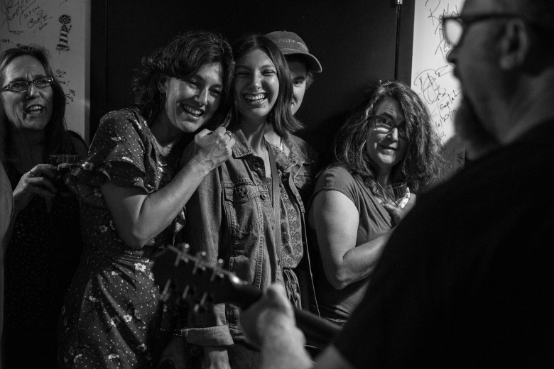 Attendee Demi Asvestas (middle) shares a moment with her mother, Lisa Asvestas (left) while Surrender by Cheap Trick is played through the halls of the Majestic Theatre dressing rooms. Photo by Scott Ball.