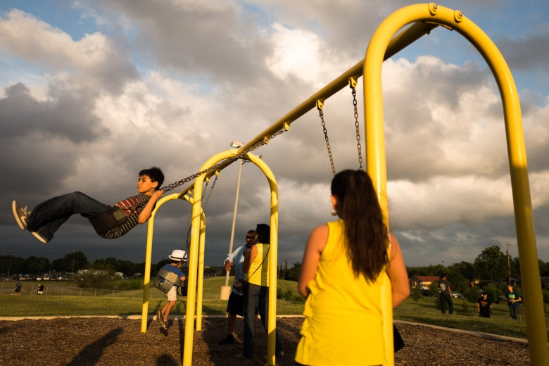 Children swing in Rosedale Park as conjunto music plays through the area. Photo by Scott Ball.