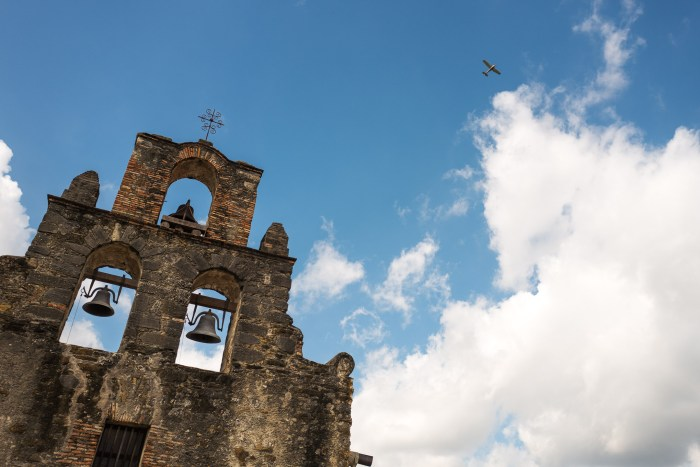 A fixed wing airplane flies over Mission San Francisco de la Espada which is near Stinson Airport. Photo by Scott Ball.