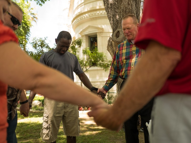Charles Amana (left) embraces hands with others in a prayer circle. Photo by Scott Ball.