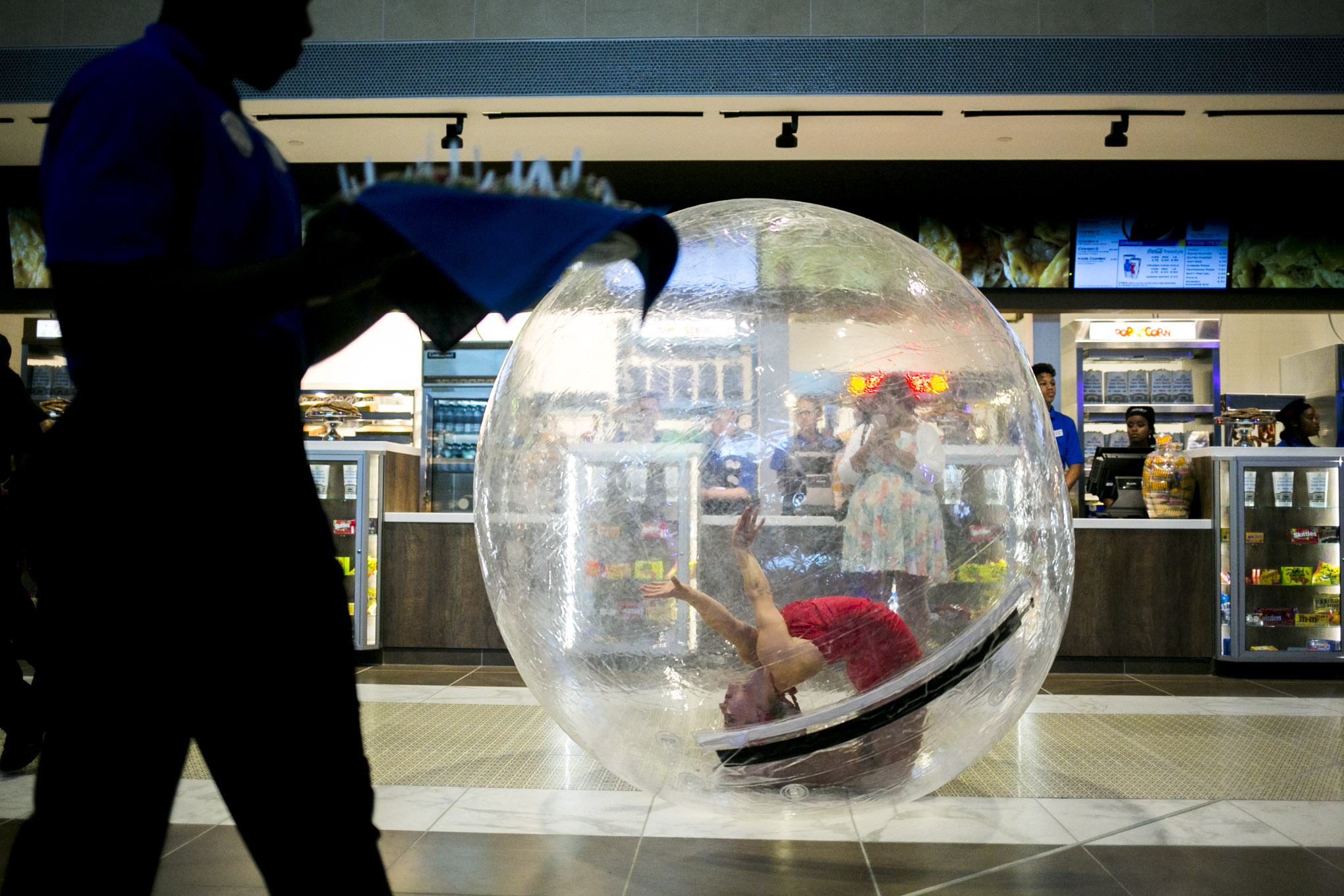 Waiters pass out food while a dancer in a plastic ball performs. Photo by Kathryn Boyd-Batstone.