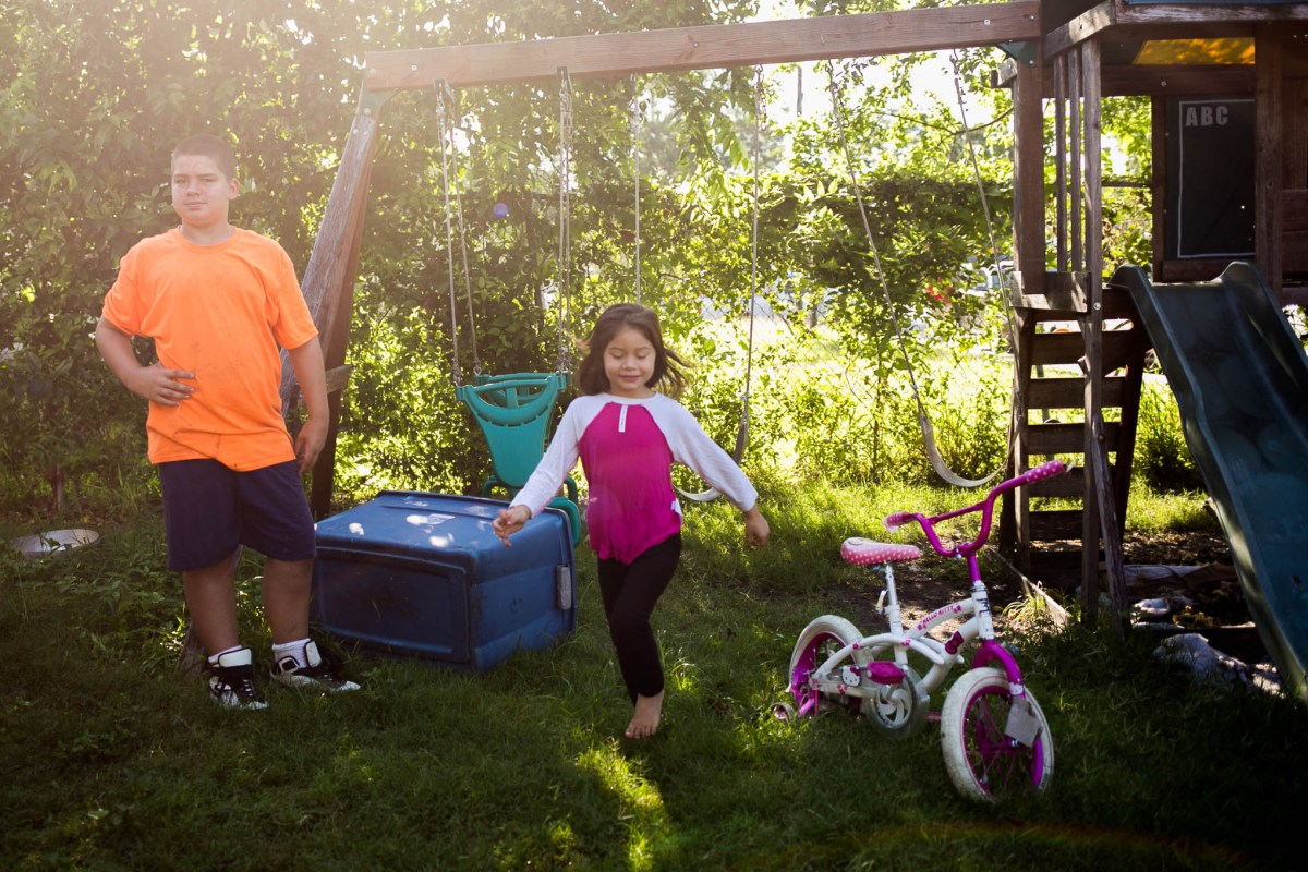 Jennifer Miller's children play in the front yard as renovations on their house begin. Photo by Kathryn Boyd-Batstone