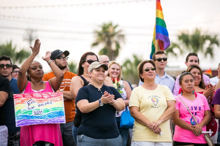 Community members clap in support of messages to stay strong and not live in fear. Photo by Kathryn Boyd-Batstone.