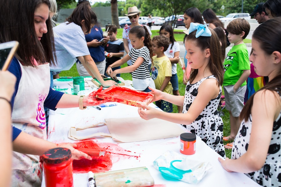 Vanessa Guerra (second from right), 7, prepares to make a screen print on a canvas bag. Photo by Michael Cirlos.