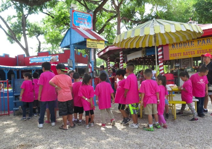 Several kids from the Boys & Girls Club of San Antonio, clad in matching pink shirts, wait in line at one of Kiddie Park's rides.  Photo by Katie Walsh.