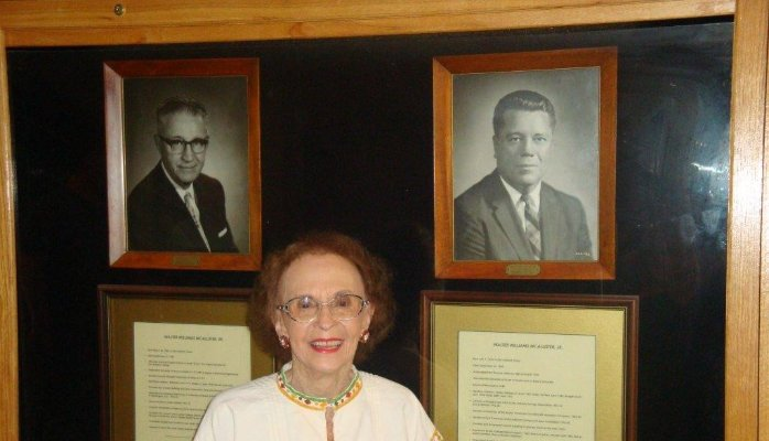 """Edith Scott McAllister stands in front of photos of her father-in-law """"Mayor Mac"""" Walter W. McAllister Sr. (left) and her late husband Walter W. McAllister Jr. Photo by Pam Tyler."""