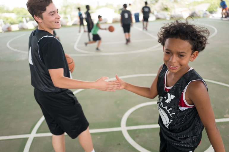 (right) Flo, 12, shakes a fellow players hand before a game. Photo by Scott Ball.