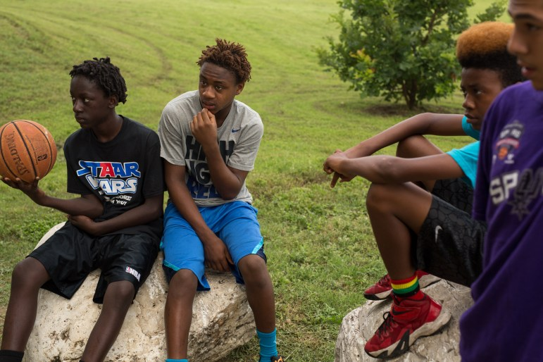 Team 'The Devastators' (left to right) Sean, 13, Keon, 13, Trevor, 12, and Timothy, 13 wait for their turn to play. Photo by Scott Ball.