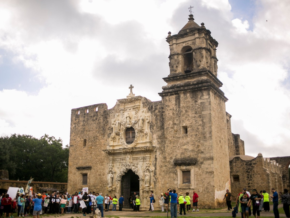 Hundreds form a line to enter the Mission San Juan church to be blessed by Holy Water. Photo by Kathryn Boyd-Batstone.